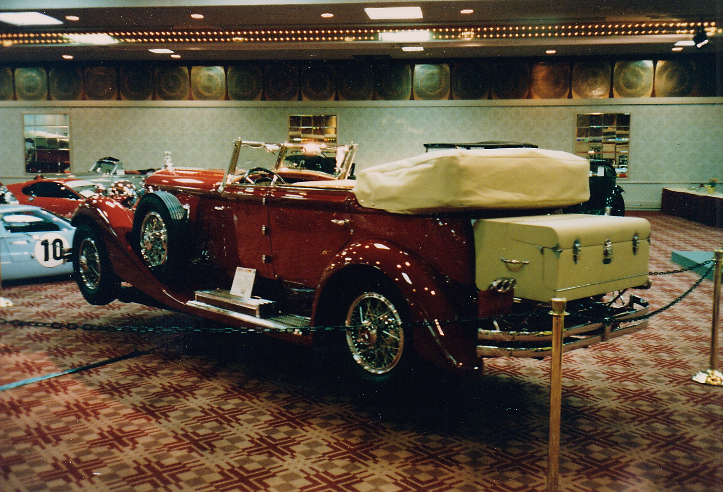 The large red open car looks like a Duesenberg, but I believe it was a Mercedes (check the grille).